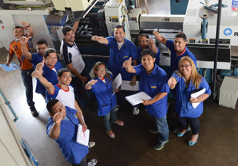 employees on factory floor giving thumbs up